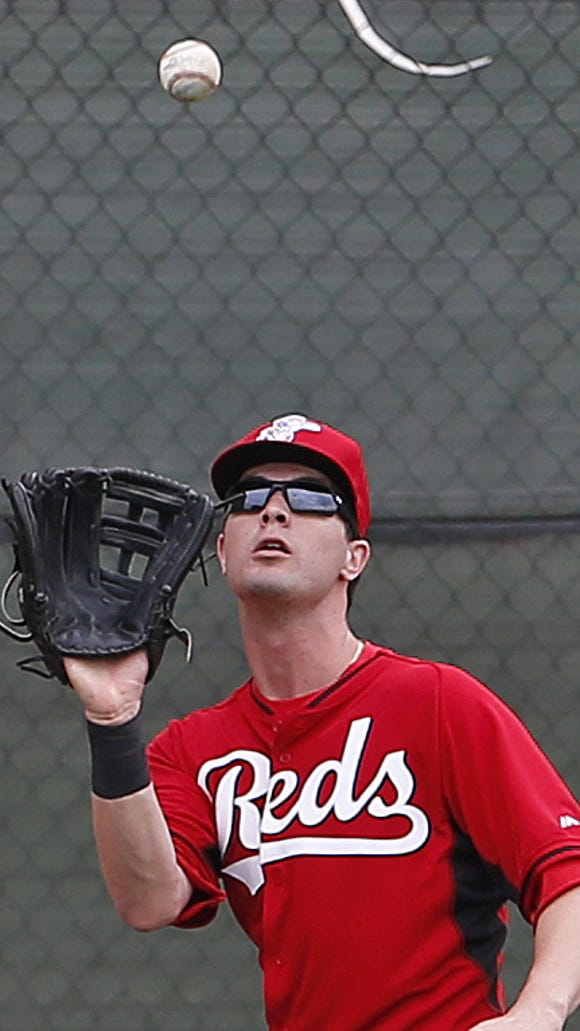 Jesse Winker catches a ball in the outfield during