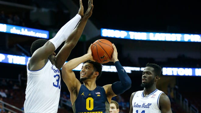 Seton Hall center Angel Delgado tries to stop the drive of Marquette guard Markus Howard on Wednesday night.