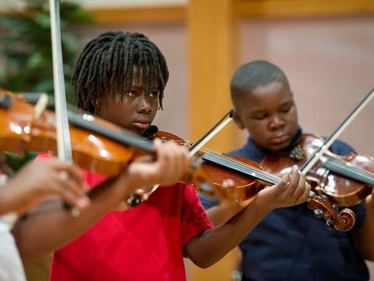 Luke Pelt (center), 11, looks up as he rehearses a
