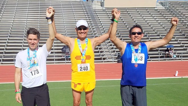 Raul Turrieta, far right, poses on the podium after he places third in the 800-meter run.