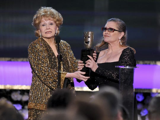 Carrie Fisher, right, presents her mother, Debbie Reynolds, with the Screen Actors Guild life achievement award in January 2015. Fisher died Tuesday at age 60, and Reynolds died a day later at 84.