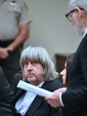 David Turpin looks on as attorney David Macher speaks during his court arraignment with wife, Louise in Riverside, Calif., on Jan. 18, 2018.
