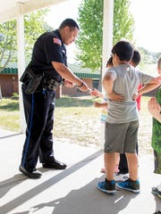 Off-duty Pensacola Police Department and school resource officer Michael Garcia hands out stickers to students at Scenic Heights Elementary School in Pensacola on Wednesday, April 18, 2018.