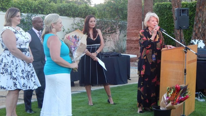 Louise Hampton welcomes the event's 200 guests, as co-principals Jennifer Geyer and Devlin Clinton, and benefit co-chairs Robin Arvai and Carmen Shelton prepare to present her with a floral bouquet.