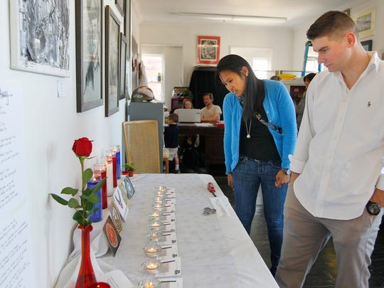 Kennedy and his wife, Zaula, view cards left at a candlelight ceremony at his art exhibit at Create Art 4 Good Studios in Rochester.