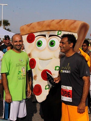 Zee Baber and Naweed Akram have their photo taken with Joey Pepperoni at the 2016 Eat My Crust 5K in Viera.