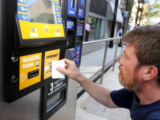 Dan Paul, with Decal Impressions, adds signage to a Cincinnati Bell Connector's kiosk reminding riders to validate their ticket. You can purchase multiple tickets in advance. You only need to validate when you're going to board the streetcar.