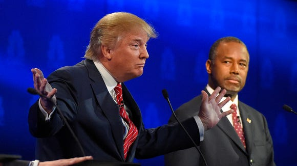 Ben Carson, right, watches as Donald Trump speaks during