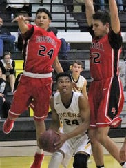 Alamogordo's Chamar Norman, center, tries to score