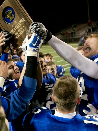 Senior captain Tyler Biadasz (52), right, hands over the sectional final trophy to the Amherst football team after winning the Level 4 football playoff game against Arcadia 42-21 at Carson Park in Eau Claire, Friday, Nov. 13, 2015.
