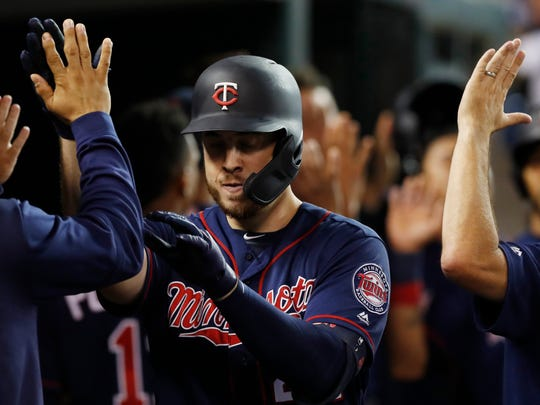 Minnesota Twins' C.J. Cron is greeted in the dugout after his three-run home run during the fourth inning of the team's baseball game against the Detroit Tigers, Friday, Aug. 30, 2019, in Detroit. (AP Photo/Carlos Osorio)