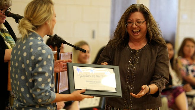 Barbara Busbee, a fifth-grade science and math teacher at Goliad Elementary, is awarded a teacher of the year certificate during a San Angelo ISD ceremony Thursday, April 28.
