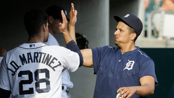 Detroit Tigers designated hitter Victor Martinez, right, high-fives teammate J.D. Martinez in the dugout before the Tigers' baseball game against the Chicago Cubs, Wednesday, June 10, 2015, in Detroit.