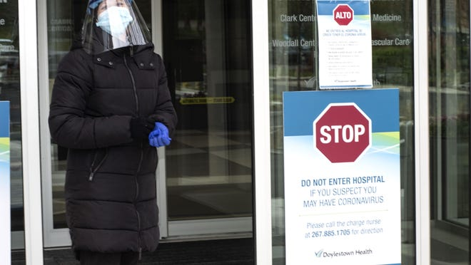 A health care worker prepares to meet visitors outside Doylestown Hospital.