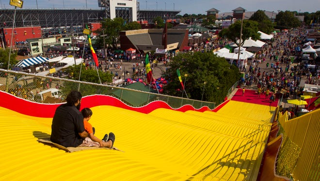 Fairgoers enjoy the Giant Slide on the opening day of the 2015 Wisconsin State Fair in West Allis.  The Giant Slide is one of the most popular permanent attractions at the fair.