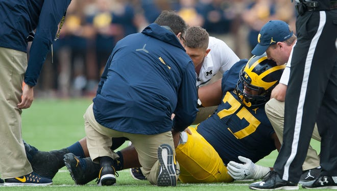 The Michigan medical staff tends to injured offensive lineman Grant Newsome during the Wisconsin game.