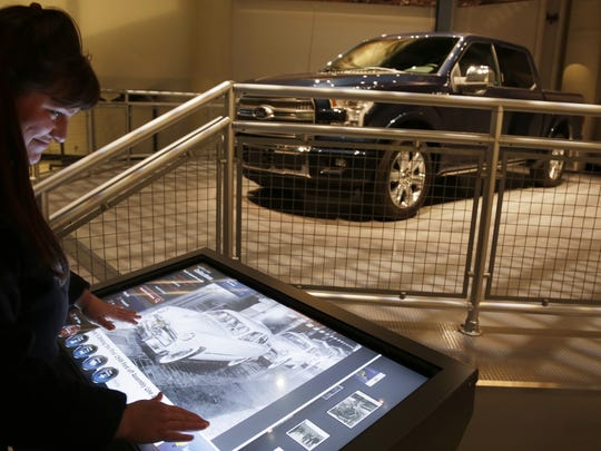 """Cynthia Jones, Ford Rouge Factory Tour general manager, demonstrates a touch screen called Collections Explorer at the new Ford Rouge Factory Tour. """"This is beyond world class,"""" Jones said. She helped design the original tour and funneled 10 years of guest feedback into the new experience."""