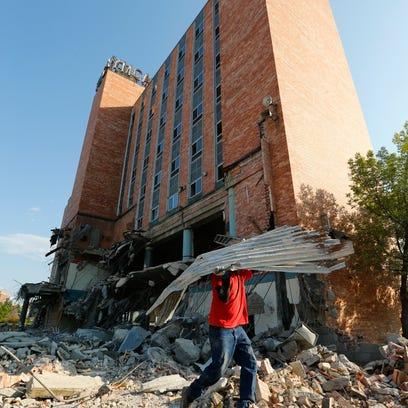 Alexis Membreno pulls scrap metal out of the rubble