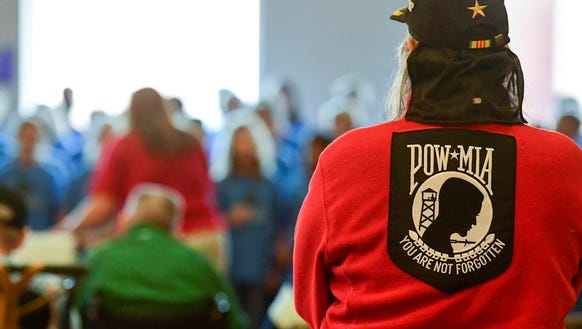 A veteran stands and listens to the choir on Friday,