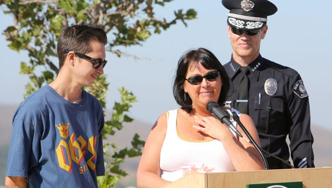 Jenifer Clark, widow of fallen Simi Valley police officer Michael Clark, with her son Bayley, speaks during a ceremony to dedicate an overpass in honor of her late husband. Police Chief Mitch McCann is in the background.
