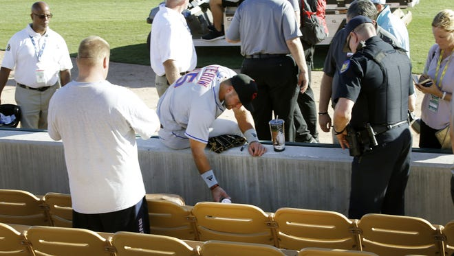 Scottsdale Scorpions outfielder Tim Tebow waits 13-minutes for EMTs to respond to a fan who passed-out following his debut against the Glendale Desert Dogs on Tuesday, Oct. 11, 2016 during the Arizona Fall League in Glendale, Ariz. Quarterback-turned-outfielder Tim Tebow signed a minor league contract with the New York Mets.