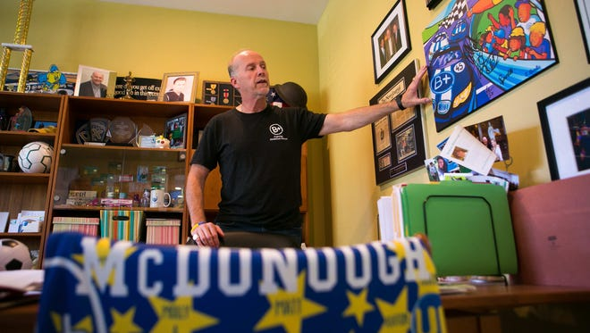 Joe McDonough stands in his home office surrounded by his son's items. McDonough founded The Andrew McDonough B+ Foundation following the death of his son who died from leukemia at 14 in 2007.