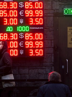 People wait to exchange currency near a sign advertising currency exchange rates at an exchange office in Moscow, Russia as the Russian ruble  came under intense selling pressure.