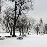 The grounds of the Marblehead Lighthouse covered in snow.