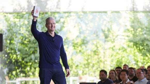 Tim Cook holding the billionth iPhone. Apple's CEO announced a planned $1 billion investment in a U.S. manufacturing fund.