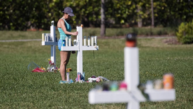 """Lisa McCrary-Tokes, a resident of Parkland, Fla., says a prayer at each of the crosses that were erected at the Parkland Amphitheatre on Friday. McCrary-Tokes lost a daughter to gun violence in Ohio last year and another daughter graduated from Marjory Stoneman Douglas High School last year. """"You can't feel safe anywhere in this country,"""" she said."""