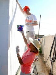 Sue Collins holds a paint bucket for Kevin McCary as