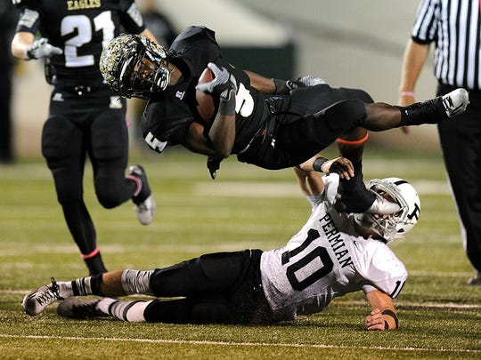 Abilene High running back David Earles (5) gets tripped up as he leaps over Odessa Permian safety Jax Welch (10) during the third quarter of the Eagles' 30-13 win on Friday, Oct. 17, 2014, at Shotwell Stadium.
