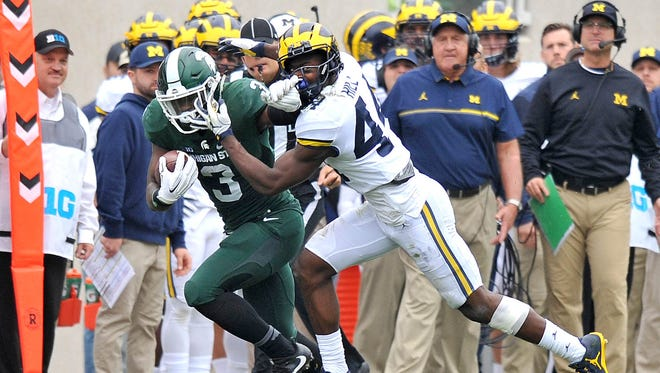 Spartan running back LJ Scott fights off Wolverine Delano Hill (44) for a long first down in front of the Michigan bench and coach Jim Harbaugh.