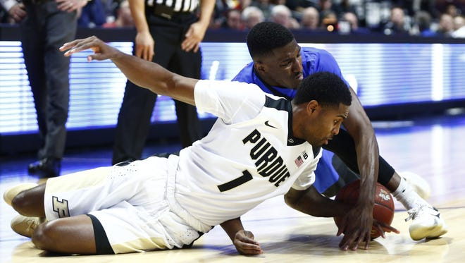 Purdue guard Johnny Hill battles for a loose ball against Florida guard DeVon Walker, back, during the first half at Mohegan Sun Arena. Purdue guard Johnny Hill (1) battles for a loose ball against Florida guard DeVon Walker (back) during the first half at Mohegan Sun Arena.