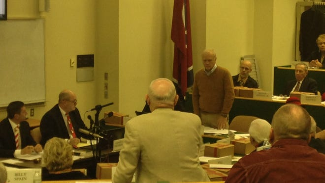 County Commissioner Jerry Bastin, left, and Smokey Roland, standing right, share information on a resolution from a committee at Monday morning's commission meeting.