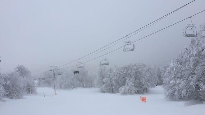 A ski lift totes skiers and riders at Bolton Valley Ski Resort on Monday.