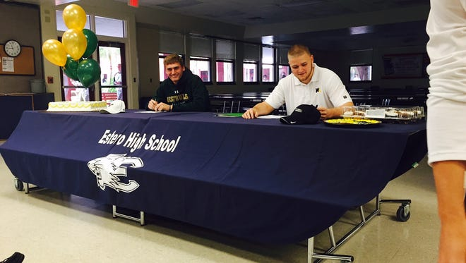 Jack Spicer and Cody Long sign their National Letter of Intents to join collegiate football programs on Wednesday at Estero