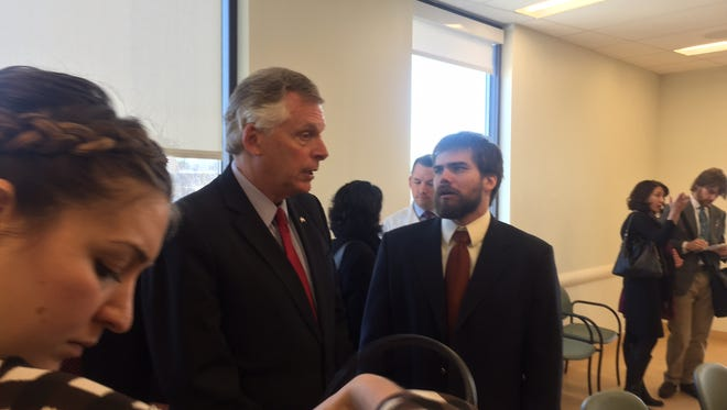 Virginia Gov. Terry McAuliffe, left, talks with Nathan Auldridge, who survived a brain tumor but couldn't get affordable insurance until Obamacare.