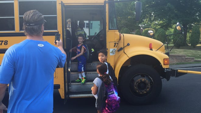 Kyle Caton, second grader at Bardonia Elementary School, gets on the school bus, while his father, Jeff, snaps a picture.