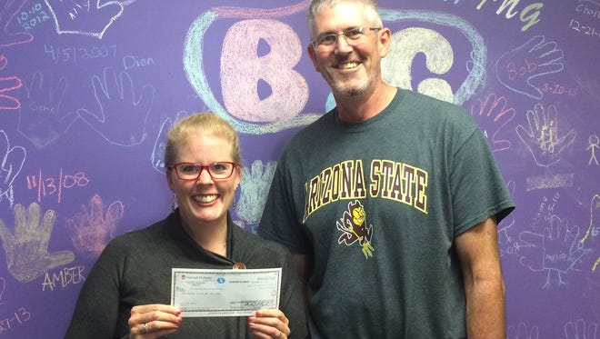 Tammy Young, executive director of BBBS, stands with Scott Page, owner of Mix it Up Bakery, who came in to drop off a check for $300.
