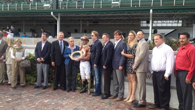 Former assistants of Hall of Fame trainer D. Wayne Lukas joined in the trophy presentation for the renamed Lukas Classic at Churchill Downs. Lukas was unable to attend because he had not yet arrived home from Philadelphia, where he wound up having surgery to insert four stents and a pacemaker.