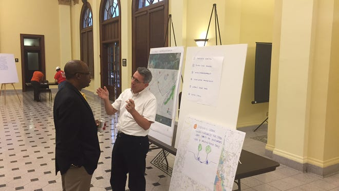 Hattiesburg Mayor Johnny DuPree, left, listens to Mississippi Development Authority consultant David Perkes talk about potential projects to mitigate flood zone damage.