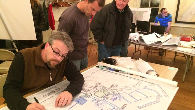 Gregg Calpino (left), from SEH, works on one of several plans for a possible Fish Creek waterfront enhancement project. Looking on are Eric Lundquist, owner of Fish Creek Scenic Boat Tours, and Fish Creek resident Wayne Kudick.