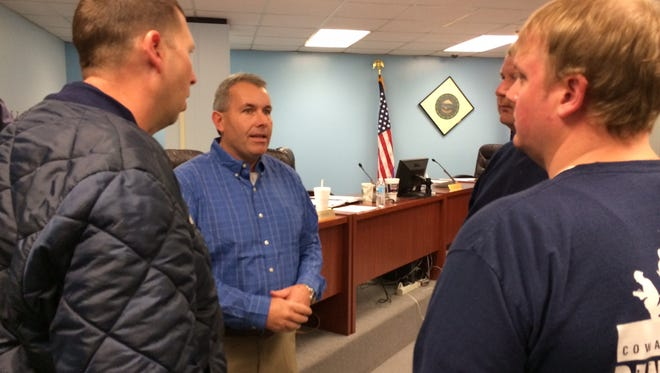 Delaware County Council member Scott Alexander talks with rural firefighters after Tuesday's council meeting. Fire departments  asked council about funds from a new public safety income tax.
