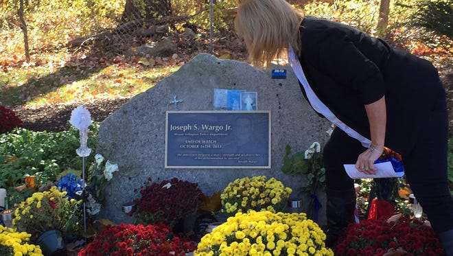 Judy Shoudy places a bouquet Oct. 26, 2015, on the Route 80 roadside memorial to the late Mount Arlington Patrolman Joseph Wargo.