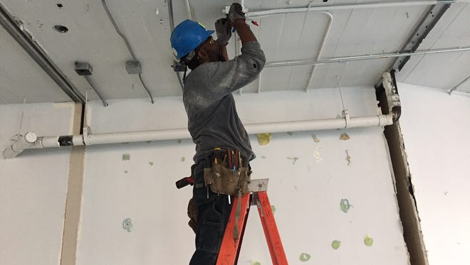 Electrician Oronde Walker works on demolition of the existing electrical system at the 1101 McGavock St. office space Google is expected to occupy.