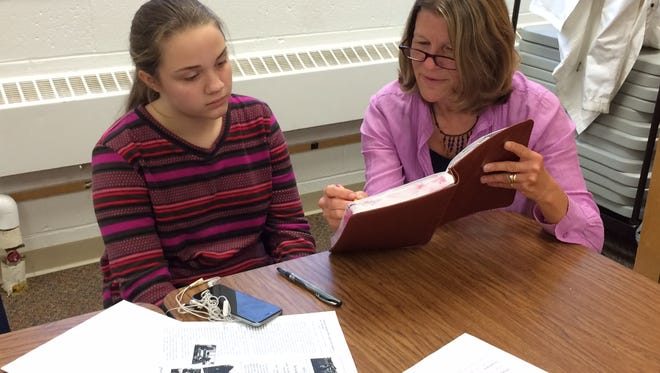 Seventh-grade student Adela Tesnow, left, works with Ann Heyse, a Write On, Door County board member, on editing her poem for the Acceptance Project.