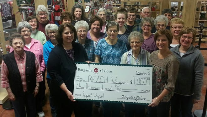 Bargains Galore recently donated $1,000 to REACH Waupun. Brenda Hofman, store manager (right), presents a check, along with a few of the store's volunteers, to Kathy Schlieve, City of Waupun Economic Development Planner (left).