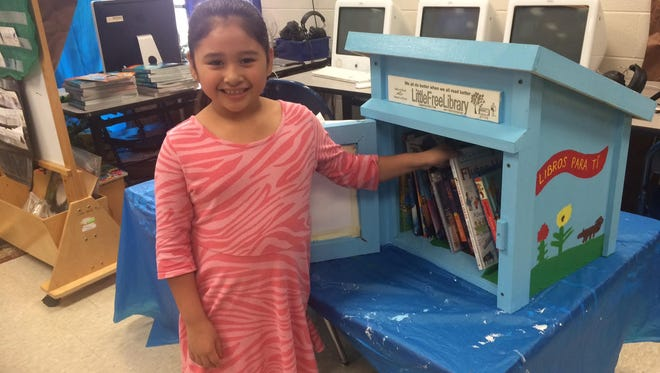 A Poplar Grove Elementary student stands next to a microlibrary the school set up in the Franklin Estates neighborhood.