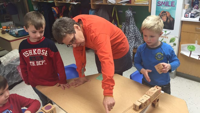 Margaret House kindergarten teacher Sue Northrup shows kids how to play with Digit Widgit and Vidget chairs.